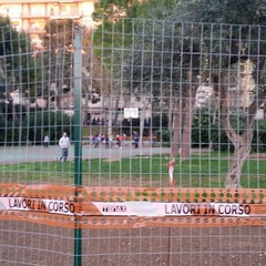 Gente a giocare nel campo da basket transennato