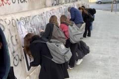 Via scritte e manifesti dalla facciata del Flacco, puliscono gli studenti