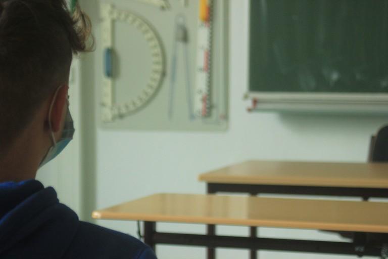 Un ragazzo a scuola con la mascherina