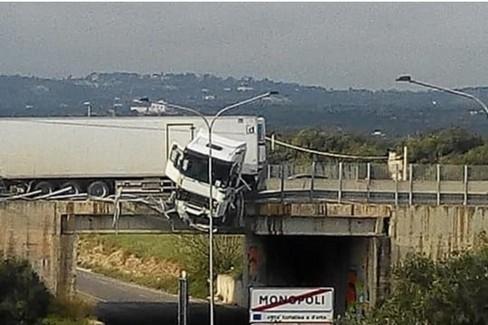 L'uscita dell'autista dal camion in bilico sul ponte